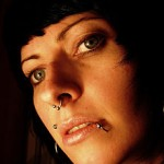 portrait_of_dark_haired_girl_with_beautiful_eyes_and_several_piercings